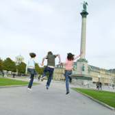 Young students jump joyfully into the air in a Stuttgart park.