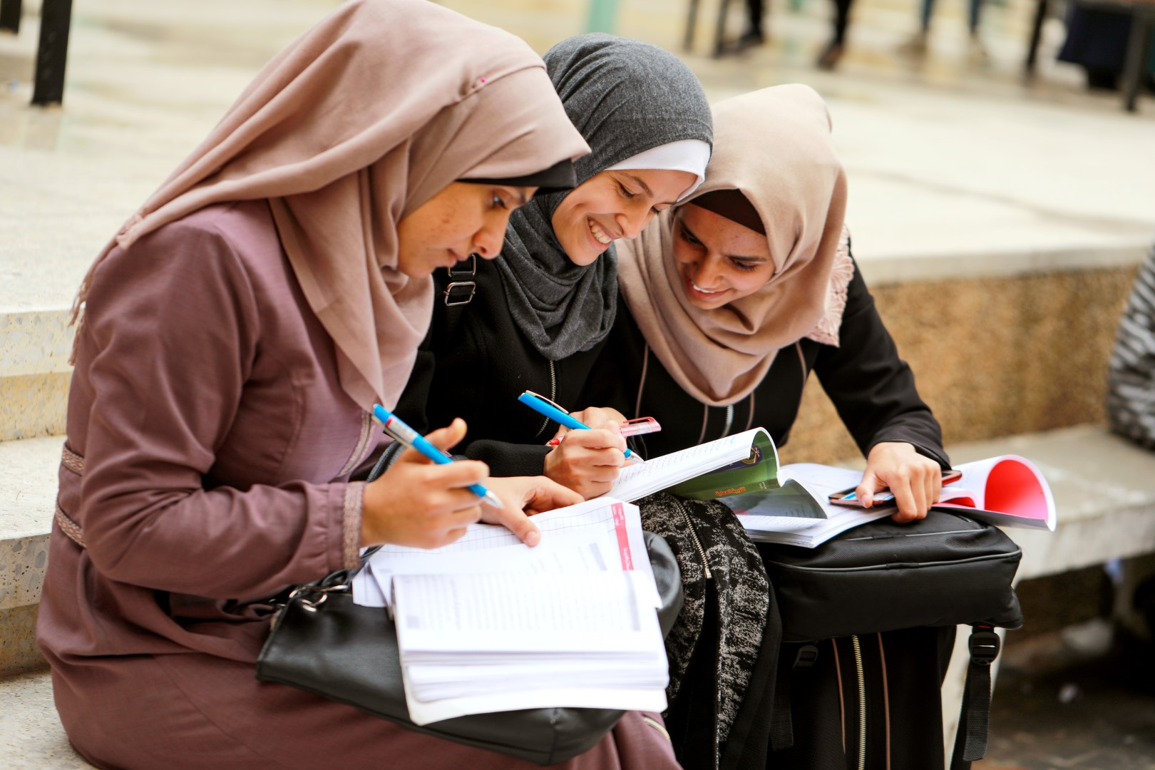 Female students discussing over books on a university campus in Gaza