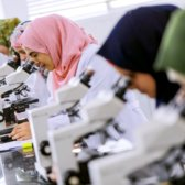 Female students looking in microscopes at a university in Gaza