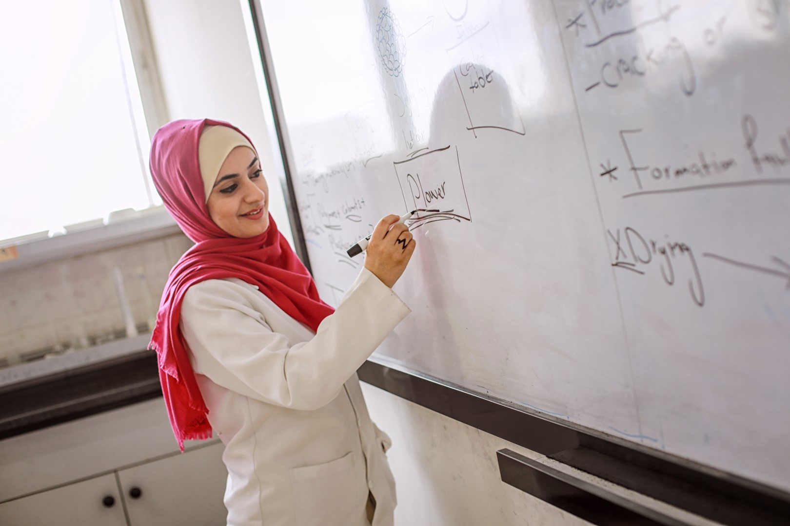 Teacher writing on white board in Gaza